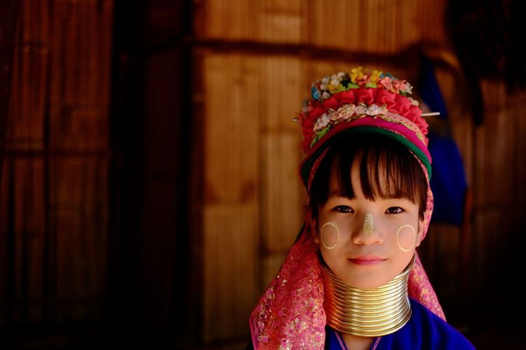 Portrait of a smiling young woman in long neck tribe traditional costume