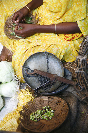 Midsection of woman selling beans in market