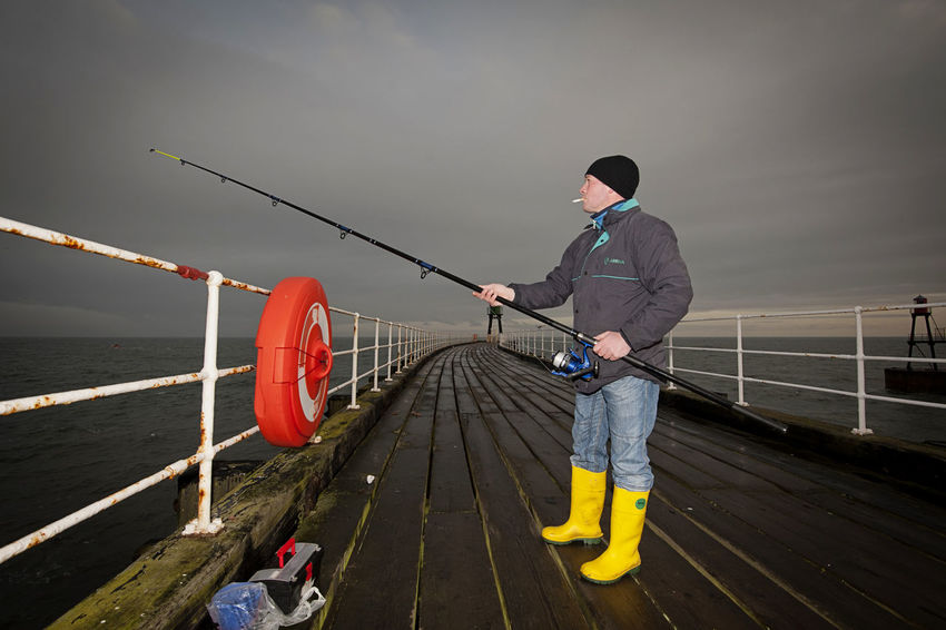 Sea fishing from the pier at Whitby in Yorkshire, United Kingdom. Cloudy Coast Coastline Expertise Fishing Fishing Rod Full Length Hobby Holding Low Light One Man Only Outdoors Outdoors Photograpghy  Outside Outside Photography Pier Railing Sea Sea Fishing Seaside Smoking