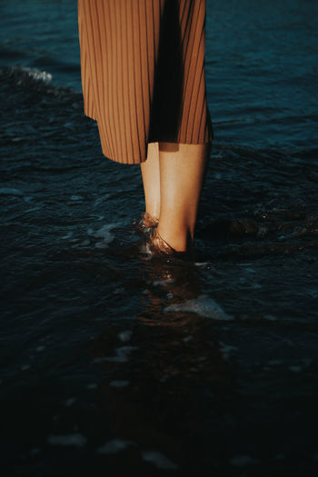 Midsection of woman standing in sea