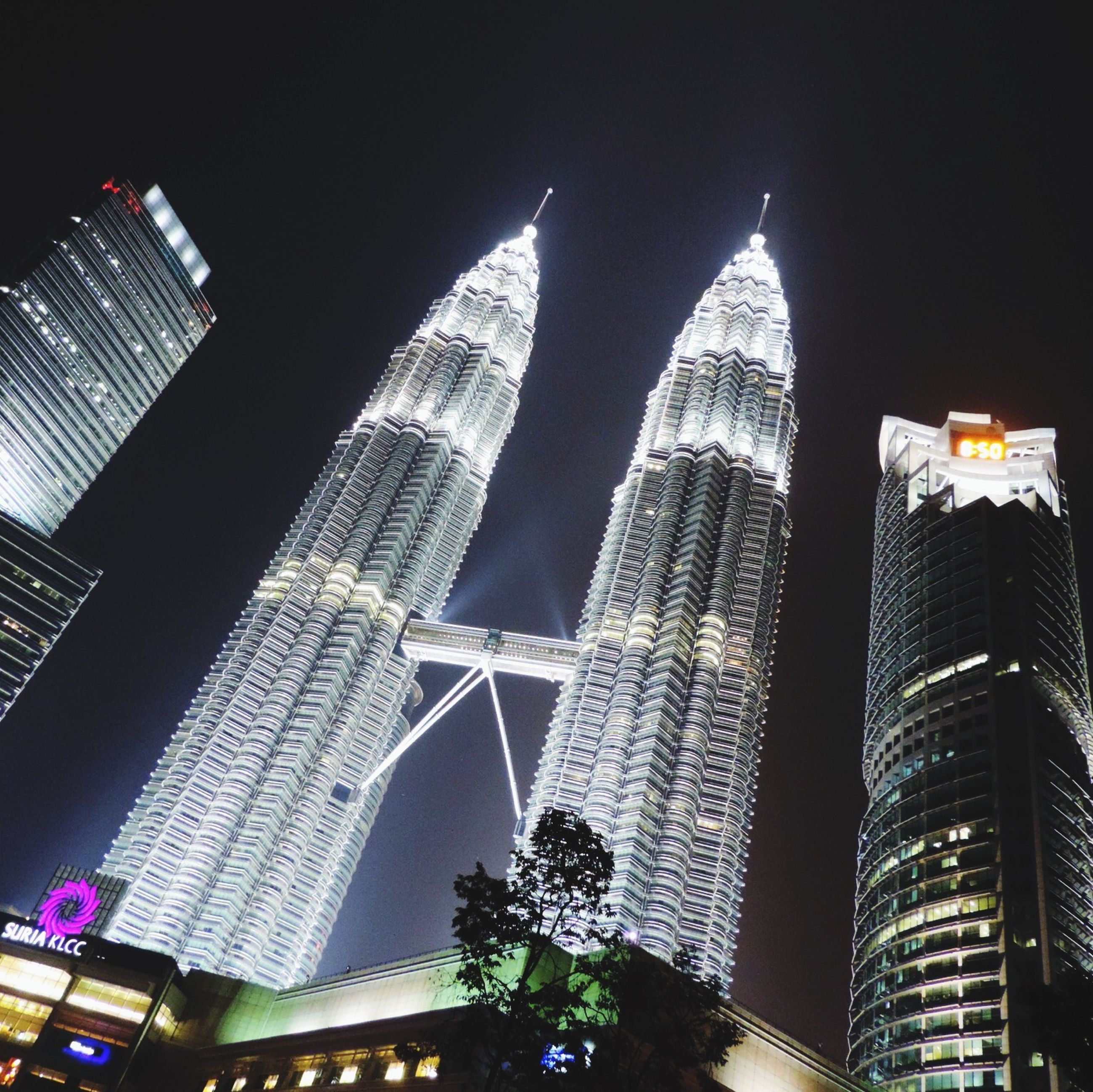 architecture, built structure, building exterior, skyscraper, city, tall - high, tower, modern, famous place, international landmark, capital cities, low angle view, office building, travel destinations, tourism, night, travel, financial district, illuminated, cityscape