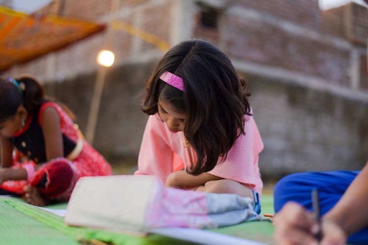 Side view of girls drawing on paper while sitting outdoors