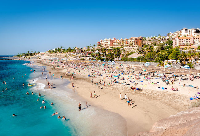 Tenerife, Canary Islands- January 5, 2015: People swimming and sunbathing on the picturesque El Duque beach, Tenerife. Canary islands, Spain Atlantic Ocean Canary Islands Coastline El Duque Beach Holiday SPAIN Swimming Vacations Beach Costa Adeje Crowd Of People Landscape Outdoors People Picturesque Relaxation Scenery Seaside Sunbathing Sunny Day Tenerife Tenerife Island Tourist Resort Travel Destinations Tropical Climate