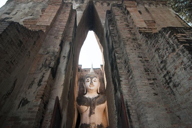 Low Angle View Of Buddha Statue At Ancient Wat Mahathat