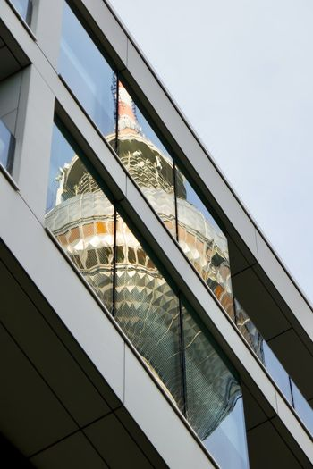 Low angle view of glass building with reflection against sky