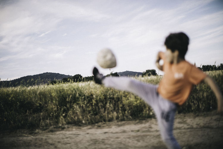 Boy playing with ball on field against sky