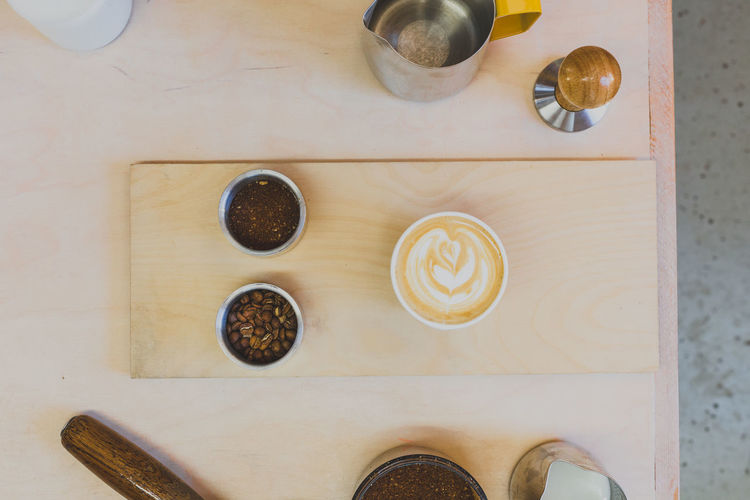 Overhead shot of coffee beans, espresso, milk, grind and latte on wooden board in coffee shop Beans Black Brown Coffee Coffee Beans Coffee Beans On Wooden Table Coffee Cup Coffee Shop Espresso Espresso Cup Filter Grind Handle Hot Drink Hot Drinks Latte Latte Art Metal Container Metal Cup Milk Overhead Pour Process Wood Wooden Board