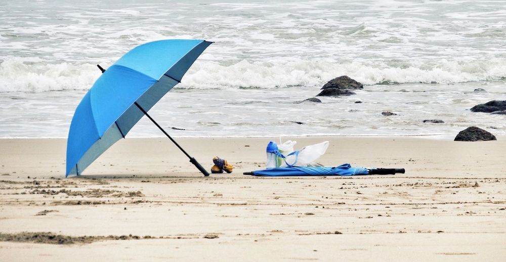 Blue umbrella and bottle on shore at beach