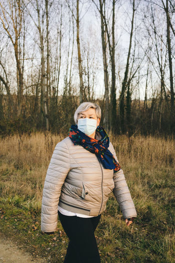 Senior woman with a face mask walking in nature
