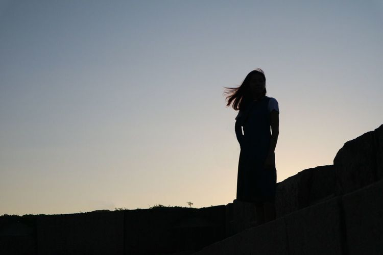Silhouette woman standing against clear sky
