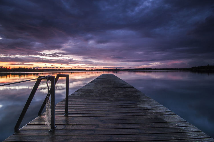 Pier over lake against cloudy sky during sunset