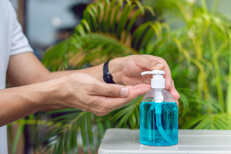 Close-up of hand holding bottle against plants