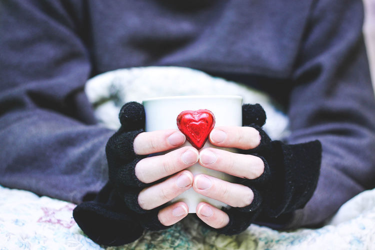 Midsection Of Person Wearing Fingerless Gloves While Holding Coffee Cup