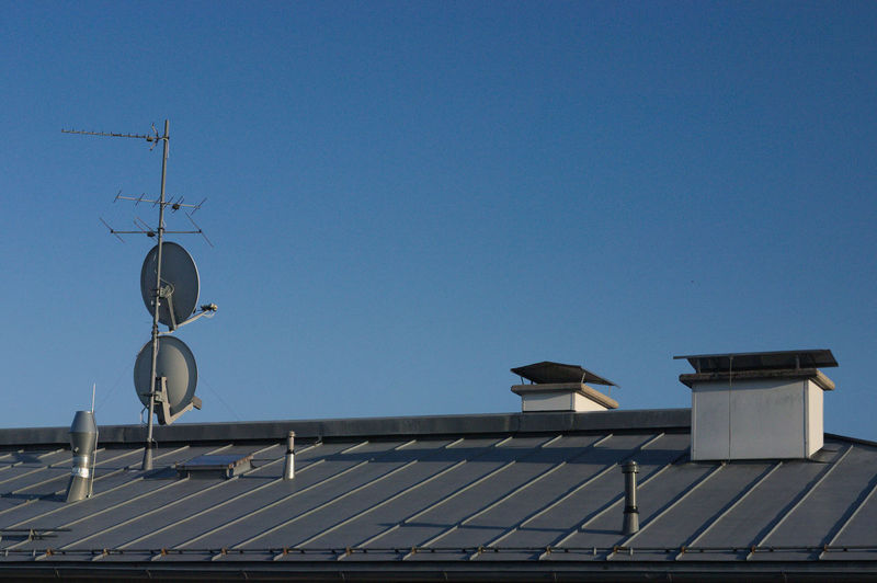 Antenna and satellite dish on house roof against clear blue sky