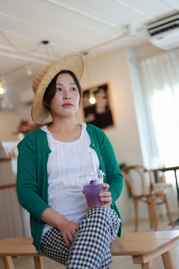 A pregnant woman in a white-green blouse is relaxed in a modern house drinking juice.