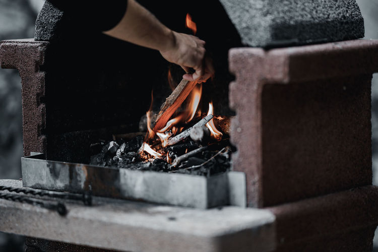 Cropped hands putting wood in fireplace