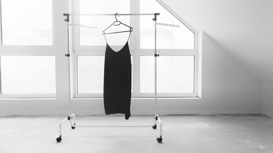 Black dress on hanger against the window