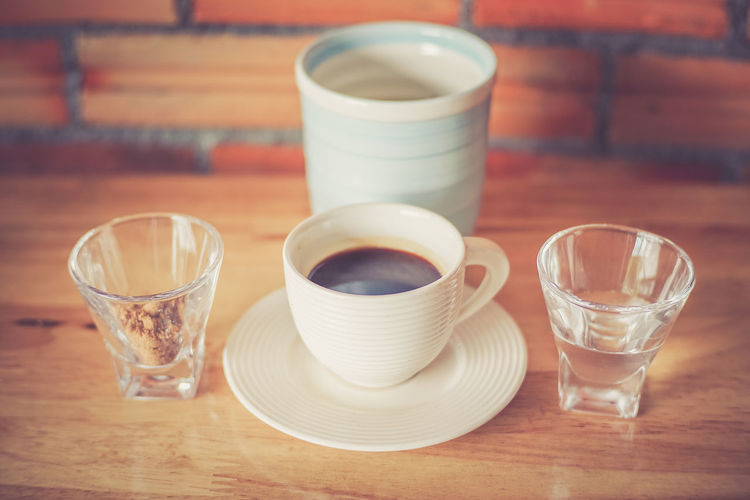 Coffee cup with brown sugar and water on table