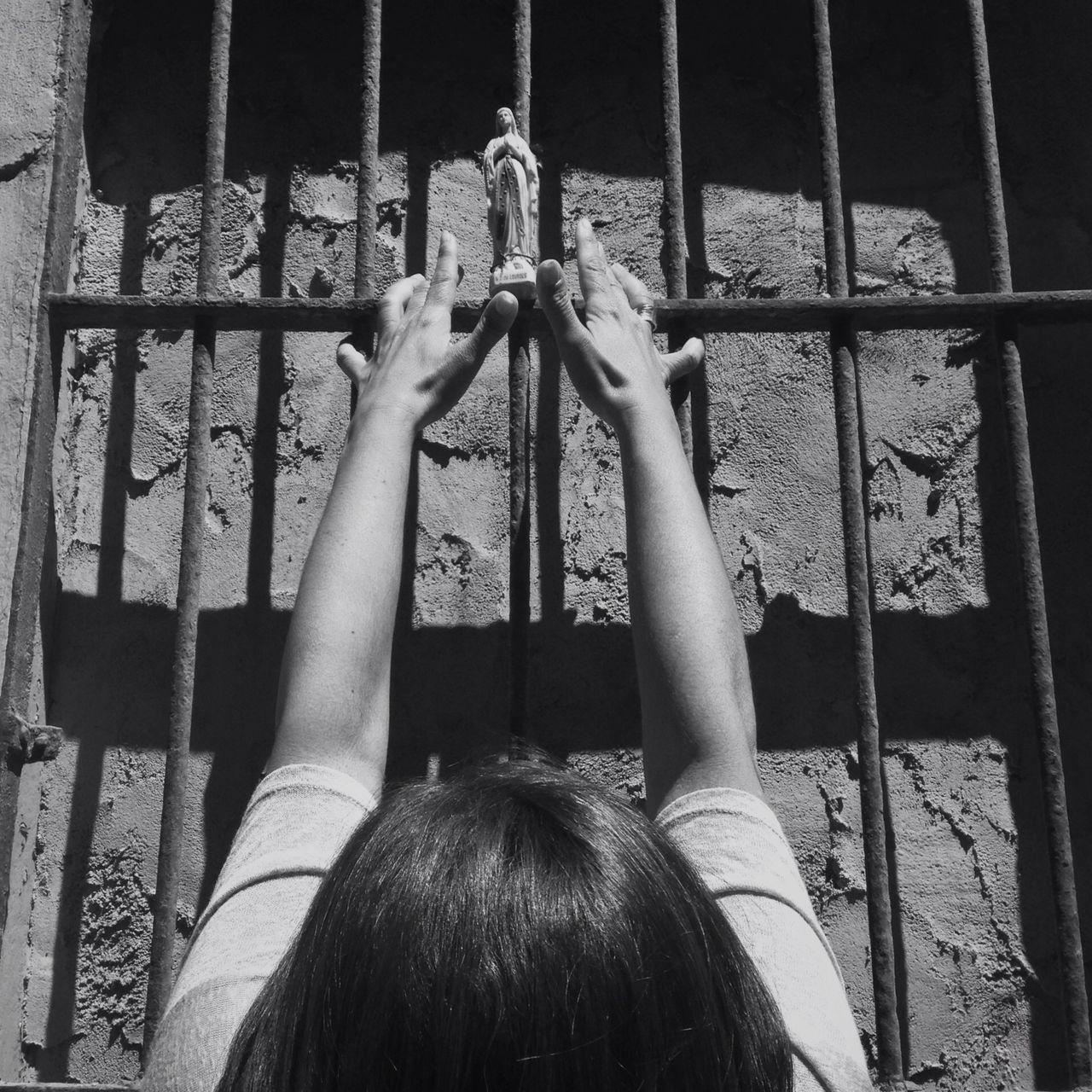 Woman praying before prison bars