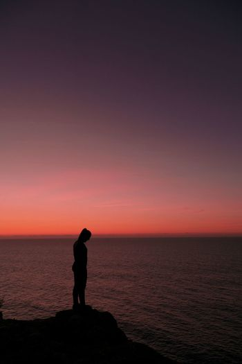 Side view of silhouette woman standing by sea against dramatic sky during sunset