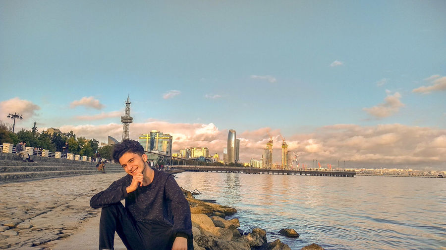 Portrait of young man sitting at riverbank against sky in city