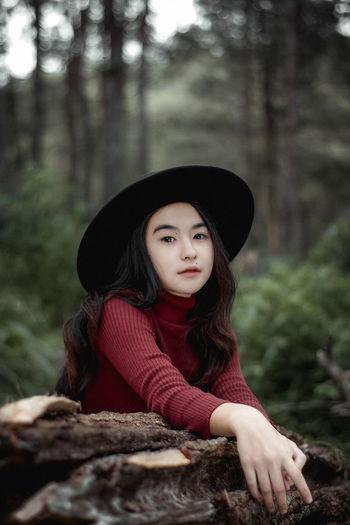 Portrait of woman wearing hat in forest