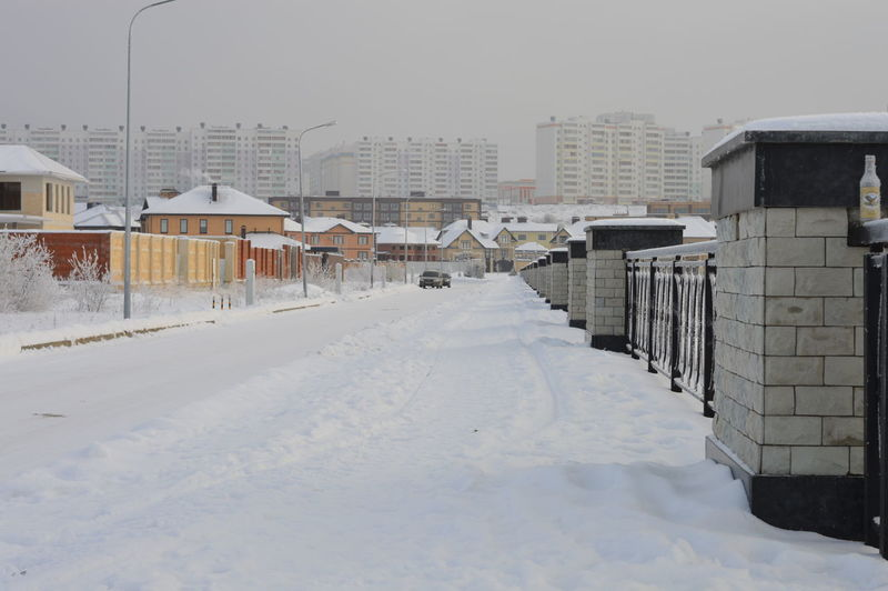 Snow covered houses by buildings in city against sky