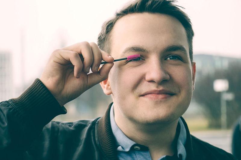 Close-Up Of Smiling Teenage Boy Using Mascara Outdoors