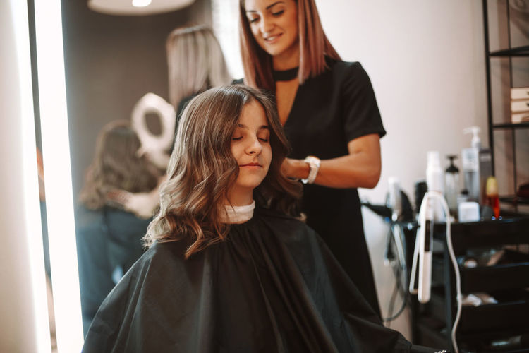 Smiling barber cutting hair of girl at salon