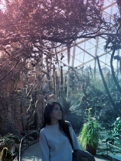 Smiling woman looking at trees and plants in greenhouse