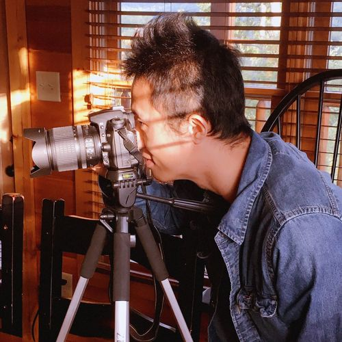 Side View Of Man Photographing With Camera Against Window Blinds