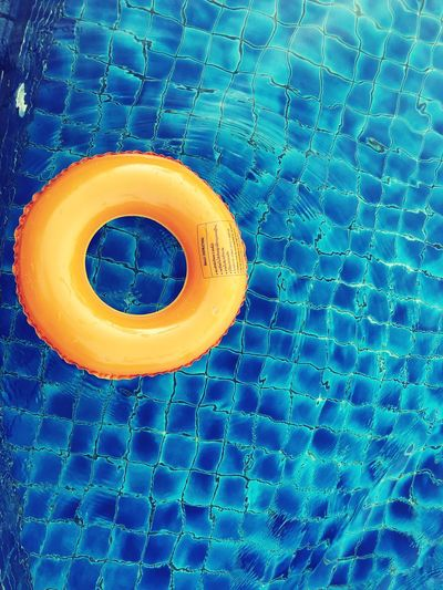 Orange floating on the blue swimming pool EyeEm Selects No People Close-up Blue Pattern Full Frame Water Geometric Shape Still Life Backgrounds Circle Indoors  Textile Shape Food And Drink Swimming Pool Day High Angle View Yellow Inflatable