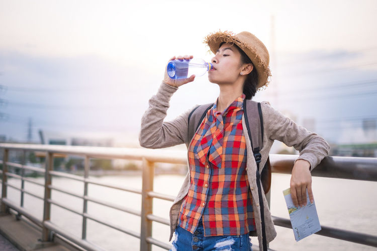 Young woman drinking water while standing against railing and sky