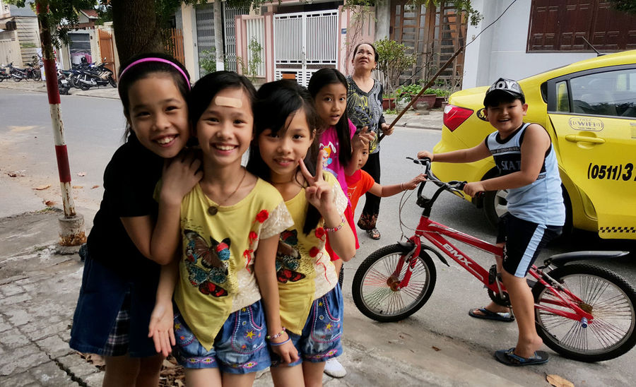 Happy children in the street in suburban Da Nang, Vietnam. Bicycles Bikes Boys Casual Clothing Children Da Nang Finger Gestures Friends Friendship Fun Girls Happiness Happy Posing Smiles Smiling Street Togetherness Twins V-signs Vietnam
