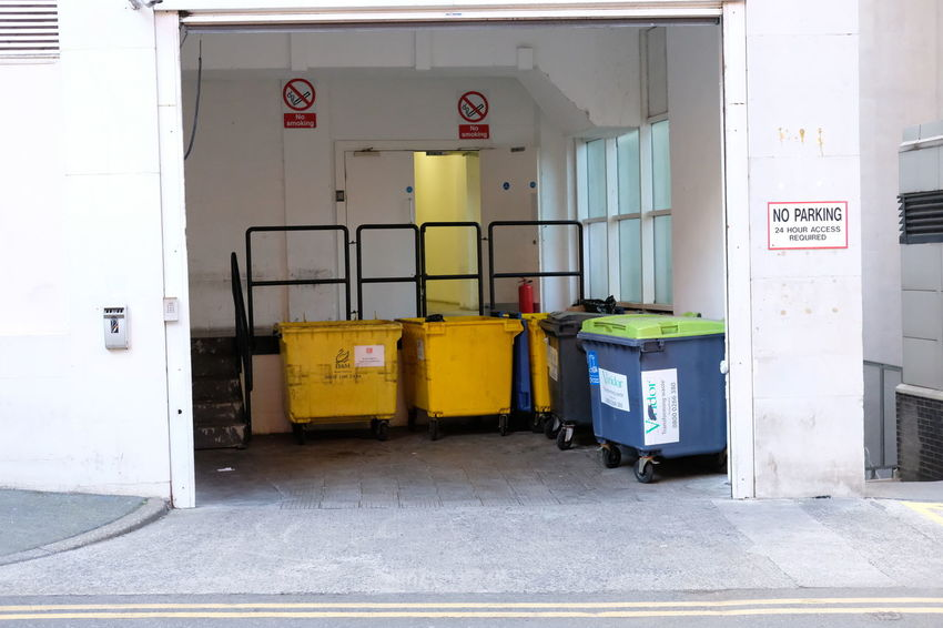 refuse area in Manchester Architecture Building Exterior Built Structure Day Door Garbage Can Hygiene No People Refuse Area Text Wheelie Bins White Walls