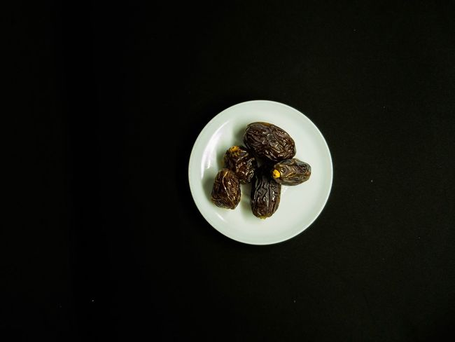 Date Palm Fruit Ramadhan Food on black background Dried Fruit Fasting Ramadhan EyeEm Selects Copy Space Food And Drink Still Life Studio Shot Indoors  No People Directly Above Freshness Food Black Background Close-up High Angle View Table Shape Sweet Food Plate