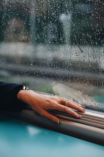 Cropped hand of woman on window sill during rainy season
