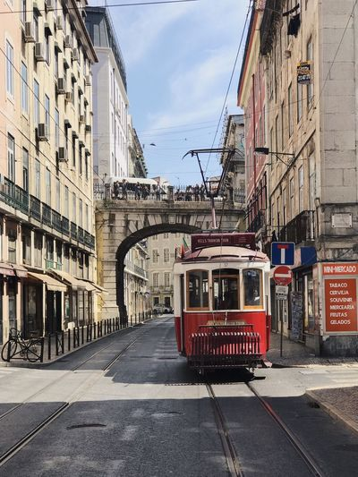 Cable car on railroad tracks amidst buildings in city