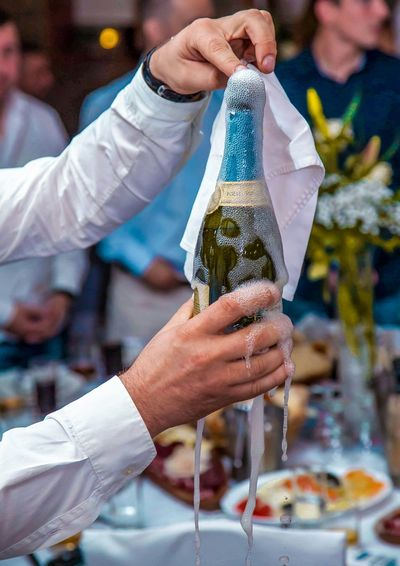 Close-Up Of Hand Opening Champagne Bottle At Wedding