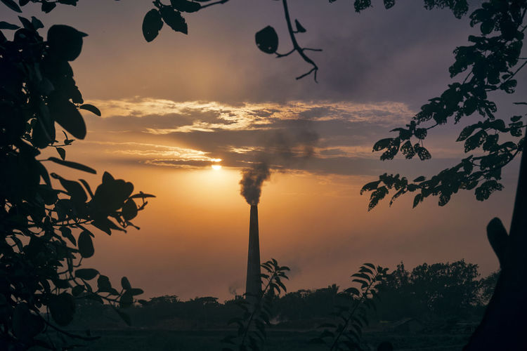 Brick field chimney, at taki in west bengal, near ichamati riverbank. photo taken during sunset.