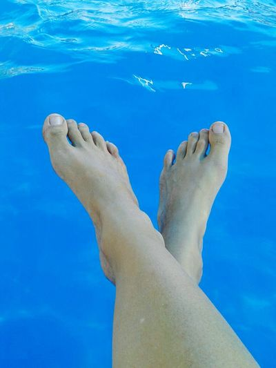 Low Section Of Woman Dangling Feet Over Water