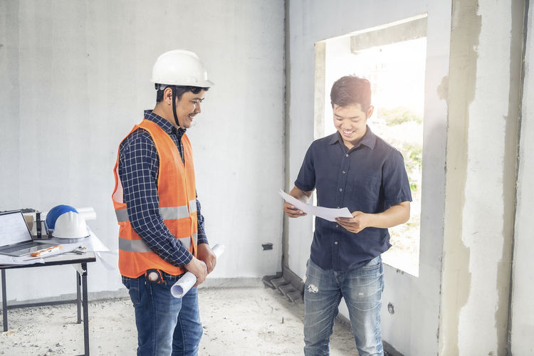 Smiling engineers holding blue prints at construction site
