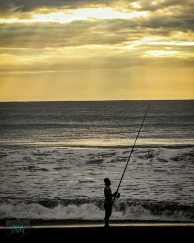 Sea Horizon Over Water Fishing Fishing Rod Fishing Pole Water Beauty In Nature Standing Sunset Weekend Activities One Person Tranquil Scene Nature Silhouette Scenics Leisure Activity Vacations Fishing Tackle Holding Beach