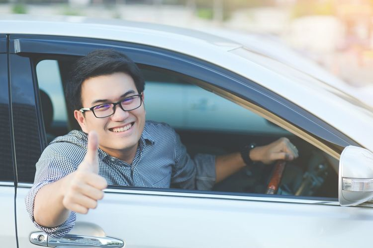 Portrait of smiling man gesturing thumbs up while sitting in car