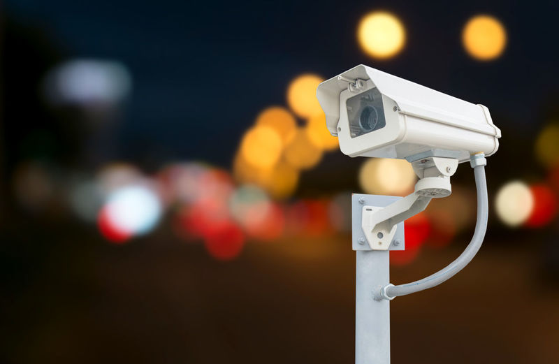 Close-Up Of Security Camera Against Illuminated Lights At Night