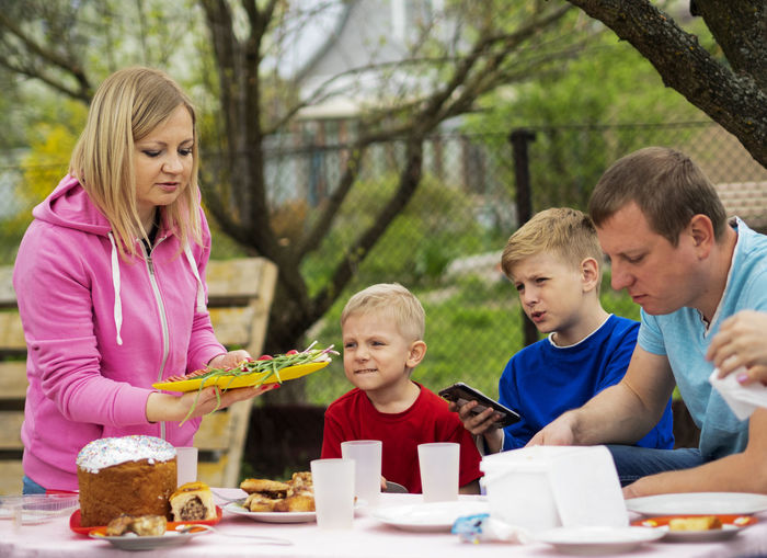 Woman serving food to sons and man outdoors