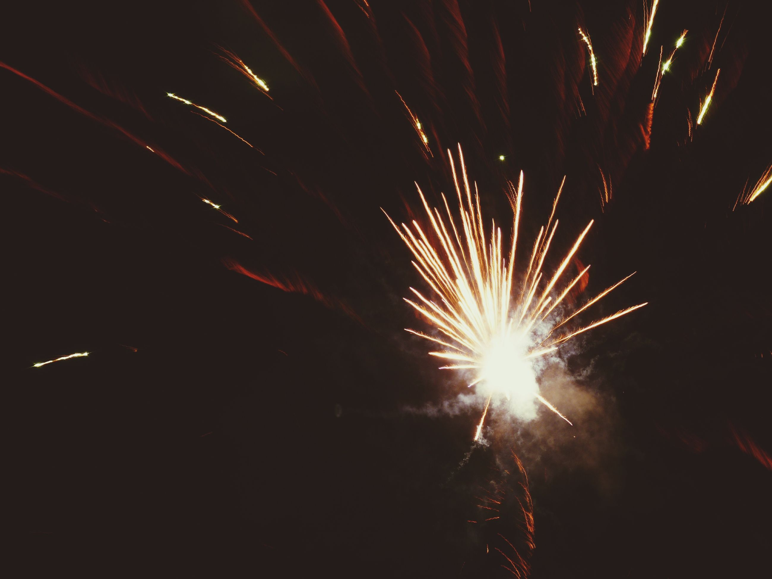 night, firework display, exploding, long exposure, illuminated, firework - man made object, glowing, celebration, sparks, motion, arts culture and entertainment, firework, low angle view, fire - natural phenomenon, event, blurred motion, entertainment, sky, smoke - physical structure, dark