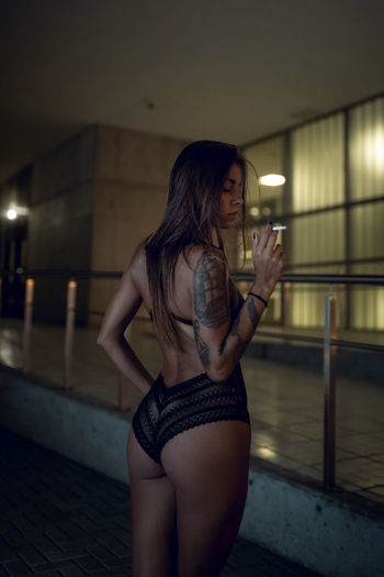 Rear view of woman wearing bikini smoking cigarette against building
