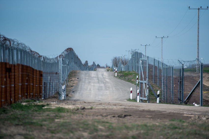 Hungarian Border Hungary Architecture Barrier Border Border Barrier Border Fence Boundary Connection Day Direction Electricity  Electricity Pylon Fence Grass Hungarian Border Fence Military Mountain Nature Outdoors Plant Power Supply Road Sky Technology The Way Forward Transportation Wire