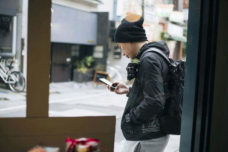 Side view of man using mobile phone